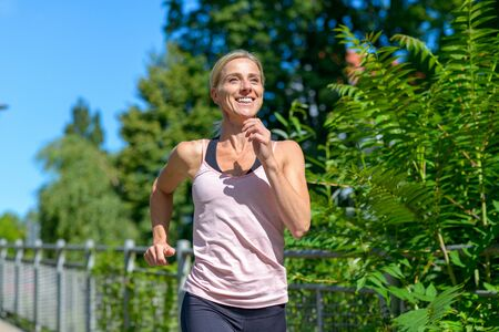 Happy healthy smiling woman full of vitality jogging outdoors along a walkway with green trees in a close up approach shot
