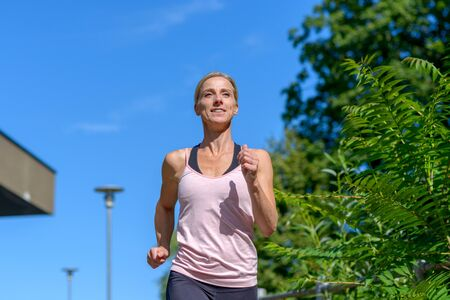 Young fit and motivated woman smiling and looking forward while running outdoors in the park in summer Banco de Imagens