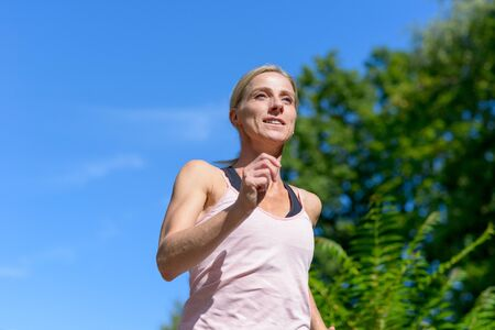 Low angle view portrait of a young fit and motivated woman smiling and looking forward while running outdoors in the park in summer Banco de Imagens