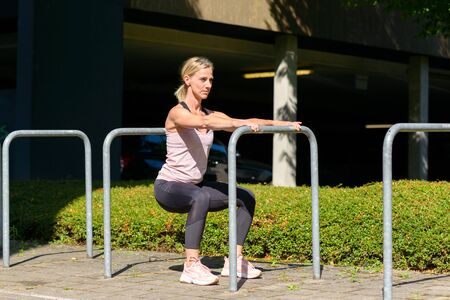 Fit muscular woman working out on bars outdoors on an urban walkway in the summer sunshine