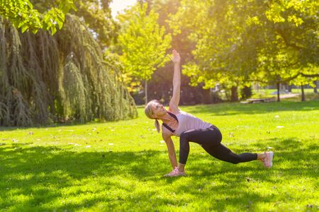 Fit woman doing lunge and stretch exercises outdoors on a lush green lawn in a park in a healthy active lifestyle concept