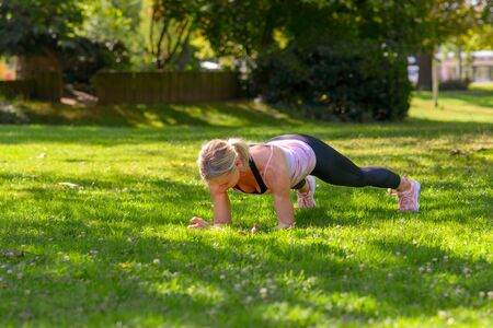 Full length view of a determined woman exercising plank on forearms for abdominal muscles during fitness training outdoors in the park in summer