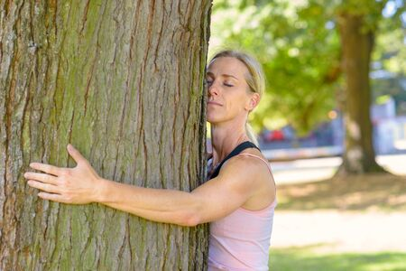 Attractive blond female nature lover hugging a tree resting her cheek against the bark with closed eyes and a serene expression in a summer park Banco de Imagens