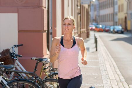 Portrait of a young fit woman in motion jogging during cardio training outdoors on the street in the city in a sunny summer morning