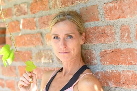 Attractive blond woman smiling at the camera as she leans against a brick wall holding fresh green leaves in her hand Banco de Imagens