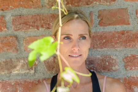 Thoughtful woman standing behind green leaves hanging on a tendril from a vine looking to the side with a quiet smile in front of a brick wall Banco de Imagens