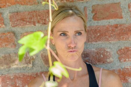 Dubious thoughtful woman pursing her lips as she stands against an exterior brick wall behind a hanging vine with green leaves in summer