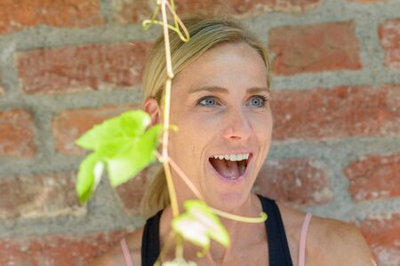 Excites blond woman reacting in amazement or astonishment looking aside with open mouth against a red brick wall with fresh green leaves in the foreground