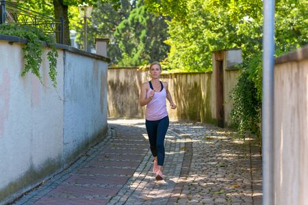 Fit woman jogging down a leafy shady lane in summer approaching the camera full length in a health and fitness concept