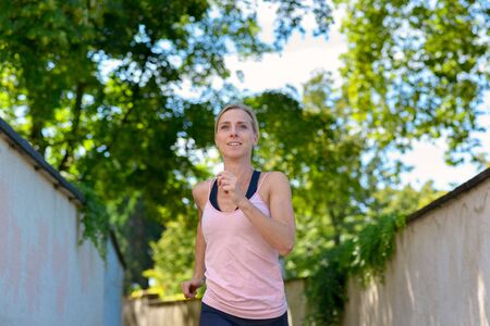 Attractive healthy fit woman jogging in summer approaching the camera along a shady lane between walls with a smile in a low angle view Banco de Imagens