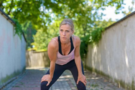 Fit muscular woman resting during a workout bending forwards with hands on knees while out jogging in a shady lane in an active outdoor lifestyle concept
