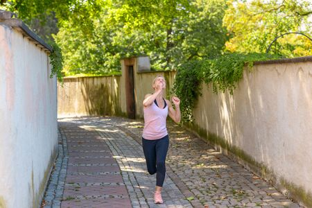Fit woman jogging under leafy green trees looking up at the foliage as she passes in a narrow urban lane in a healthy lifestyle concept Banco de Imagens