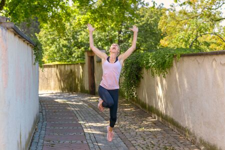 Happy fit healthy woman celebrating leaping in the air while jogging along a shady lane in summer