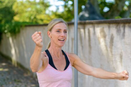 Happy woman celebrating punching the air with her fists as she jogs along a shady lane in summer in a fitness concept Banco de Imagens