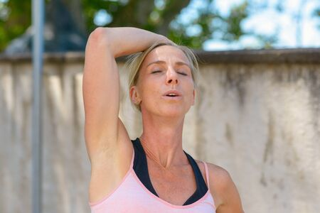 Attractive blond woman with a thoughtful friendly smile raising her arm above her head with closed eyes