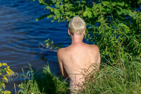 Back view of an attractive blond nude woman at the lake
