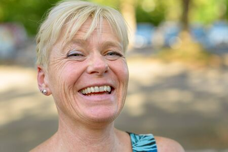 Portrait of an attractive older blond laughing woman outdoors in a park looking to the camera