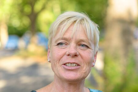 Close up portrait of an attractive older blond smiling woman looking to the side outdoors in a park