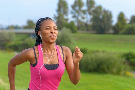 Porträt einer glücklichen jungen Afrikanerin, die auf einem ländlichen Fußweg joggt und Musik hört
