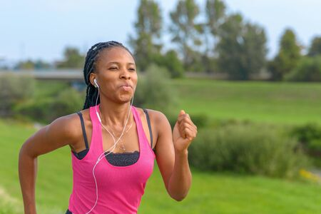 Ritratto di una giovane donna africana felice che fa jogging su un sentiero rurale ascoltando musica