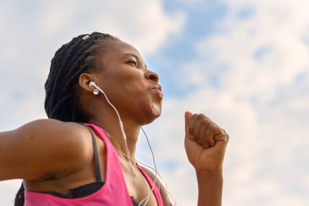 Determined young African woman working out jogging listening to music as she runs outdoors in a close up low angle view against cloudy sky