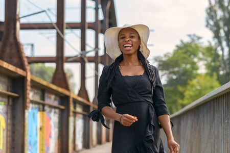 Laughing vivacious young African woman wearing braided hair extensions and a stylish wide brimmed straw hat