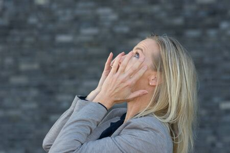 Screaming blond woman with hands to her cheeks viewed from her side in close-up, standing outdoors in grey coat against dark grey background