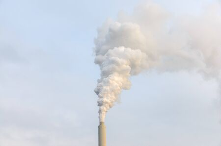 Dirt smoke billowing from an industrial chimney into a smoky sky in a concept of atmospheric pollution and global warming