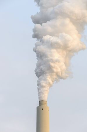 Portrait of an smoke billowing from an industrial chimney into a smoky sky in a concept of atmospheric pollution and global warming