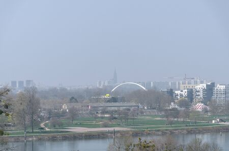Modern city on a misty or smoggy day with reduced visibility of a waterfront park and downtown buildings with a view to an arched bridge in the distance