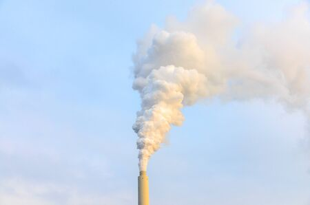 Smoke billowing from an industrial chimney into a smoky sky in a concept of atmospheric pollution and global warming
