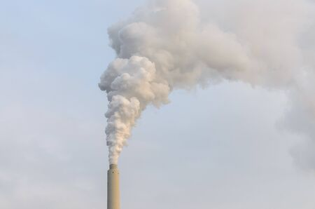 Grey clouds of smoke belching from an industrial chimney in a concept of air and atmospheric pollution, global warming and climate change Imagens