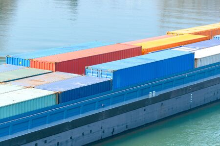 Close up on freight containers on a ship or barge in a concept of international marine industrial haulage, trade, import and export Stock Photo