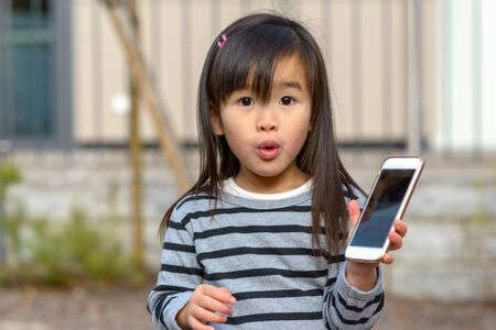 Adorable little girl with a look of awe and amazement pursing her lips at the camera as she holds up a mobile phone in her hand outdoors in front of a building