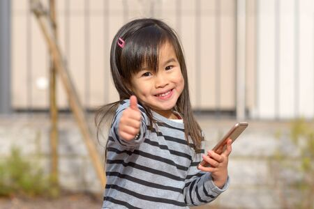 Cute happy young girl with dimples smiling at the camera as she gives a thumbs up gesture with her hand while holding a mobile phone outdoors in sunshine Stock Photo