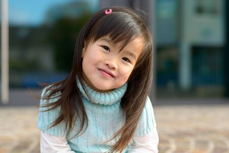Friendly young girl with a sweet happy smile sitting outdoors looking quietly at the camera in a close up portrait