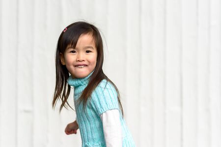 Cute young Asian girl swinging around to look at the camera with a happy smile outdoors over a white textured background with copy space