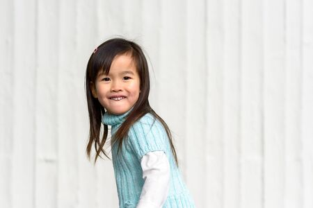 Fun loving playful pretty little Asian girl swinging round to face the camera with a happy grin outdoors against a textured white wall with copy space