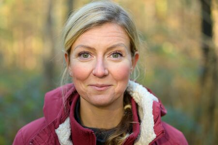 Adult blond woman in her forties, wearing warm red jacket smiling and looking at camera, while standing outdoors in the forest. Bust front portrait 스톡 콘텐츠