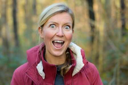 Blond woman in red jacket outdoors showing funny grimace expressing extreme excitement or happy surprise, gazing at camera with eyes wide and with open mouth
