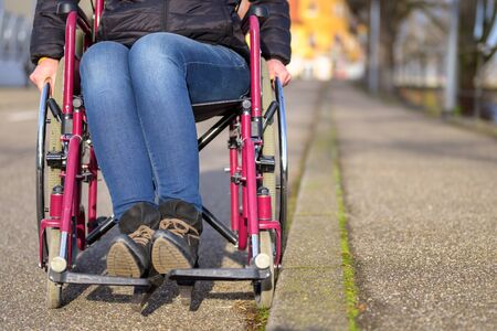 Feet of a disabled woman seated in a wheelchair at the edge of an urban street against the curb in a low angle view