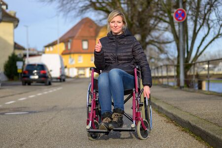 Smiling handicapped woman using a wheelchair in an urban street giving a thumbs up to show her positive attitude Фото со стока