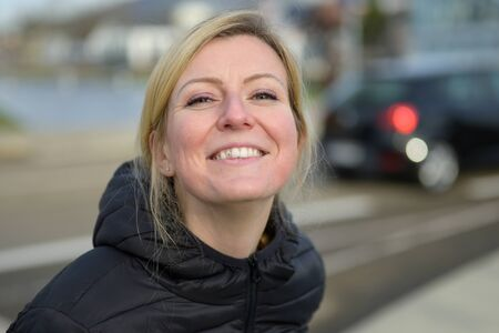Cute young blond woman with an impish grin lifting her face to the camera in an urban street Imagens