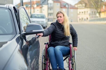 Handicapped woman in a wheelchair opening a car door to enter off a quiet urban street with a troubled expression of stress in a concept of mobility and disability
