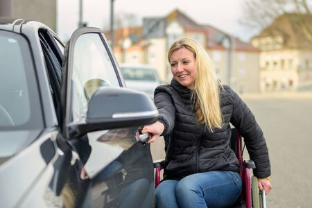 Handicapped woman in a wheelchair opening a car door in a quiet urban street as she prepares to enter the car with a happy smile in a concept of overcoming disability