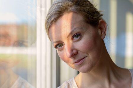 Fragende blonde Frau mit einem wissenden Lächeln, die in der Nähe eines Fensters steht und das Licht auf ihrem Gesicht reflektiert, das leise in die Kamera lächelt