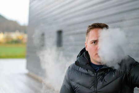 Young man in his twenties addicted to smoking standing outdoors vaping on an e-cigarette blowing a cloud of smoke towards the camera with copy space Archivio Fotografico