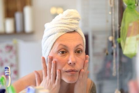 Woman wearing a towel on her wet hair after showering taking a close look at her face in a bathroom mirror in a personal hygiene concept