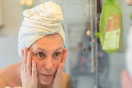 Middle-aged woman examining her face in a mirror in the bathroom after showering with her hair wrapped in a towel in a personal hygiene concept