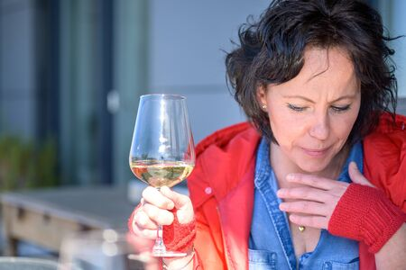Woman coughing holding her hand to her chest with respiratory distress as she enjoys a glass of wine outdoors in a concept of symptoms of the coronavirus or Covid-19 Stock Photo